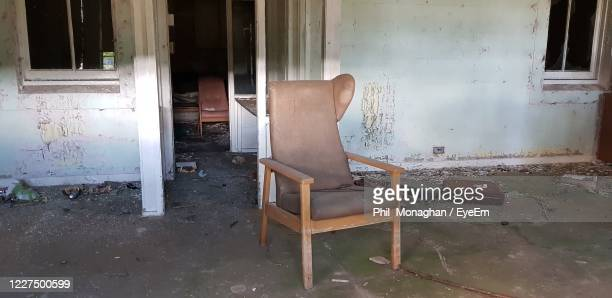abandoned chair against old building - chair stock pictures, royalty-free photos & images