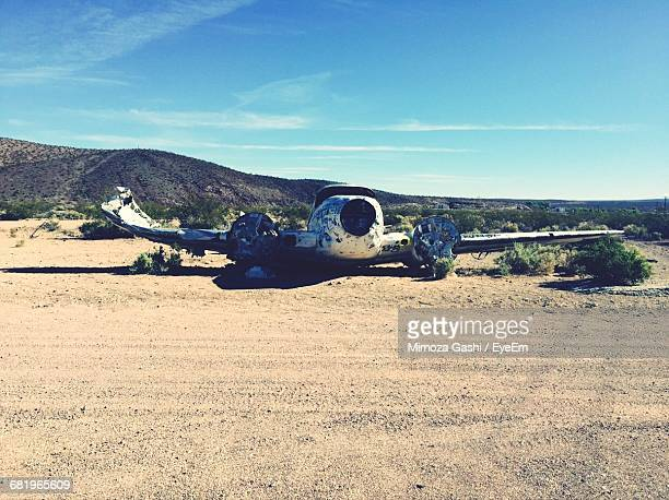 Abandoned Crashed Airplane On Field By Dirt Road Against Sky