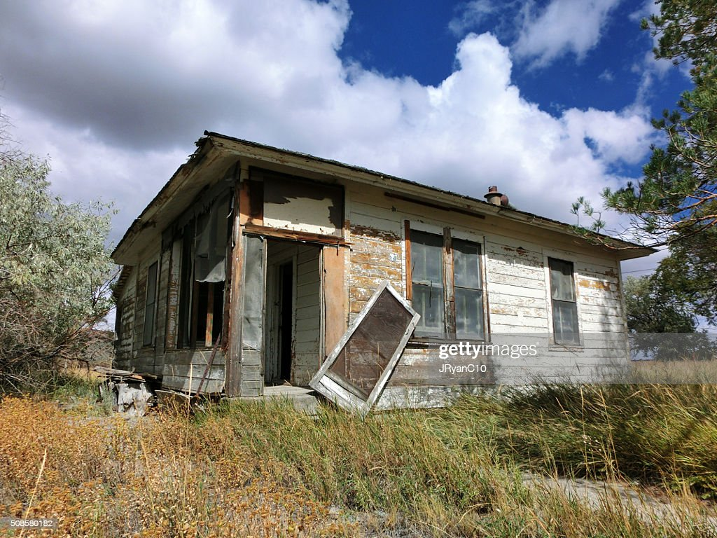 Abandoned crumbling wooden house on prairie : Stock Photo