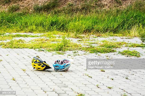 Abandoned Cycling Helmets On Cobblestone Street Against Grass