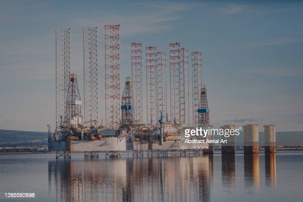 abandoned drilling rigs photographed from the shore, cromarty firth, scotland, united kingdom - economy stock pictures, royalty-free photos & images