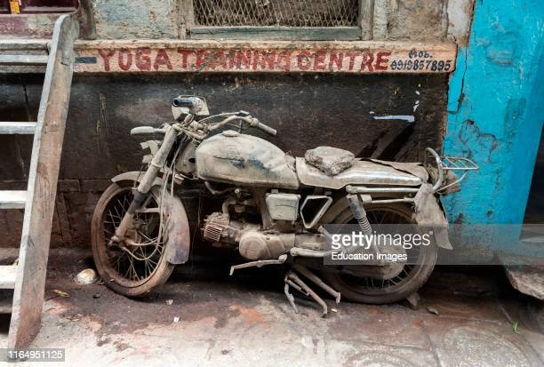 Abandoned dusted motorcycle in the streets of Varanasi Old City India