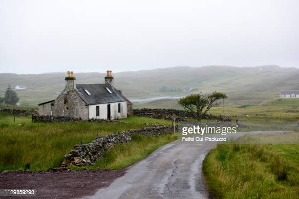 abandoned farmhouse and single lane road near lochinver, sutherland, scotland. - schotland stockfoto's en -beelden