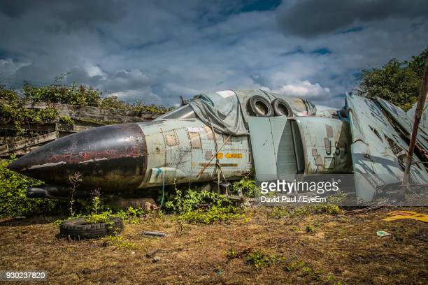 abandoned fighter plane on field against sky - coventry stock pictures, royalty-free photos & images