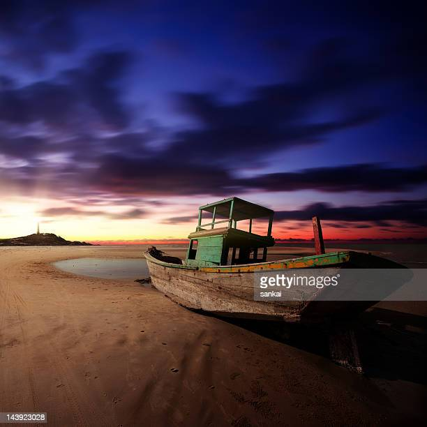 Abandoned fishing boat on the beach at sunrise