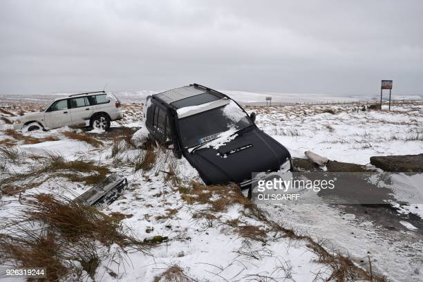 TOPSHOT Abandoned four wheel drive vehicles are pictured in snowcovered moorland beside the A672 near to the M62 motorway north east of Manchester in...