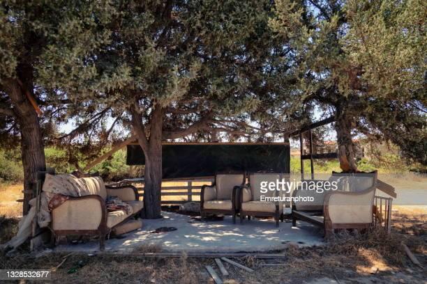 abandoned furniture under a tree on a sunny day. - emreturanphoto fotografías e imágenes de stock