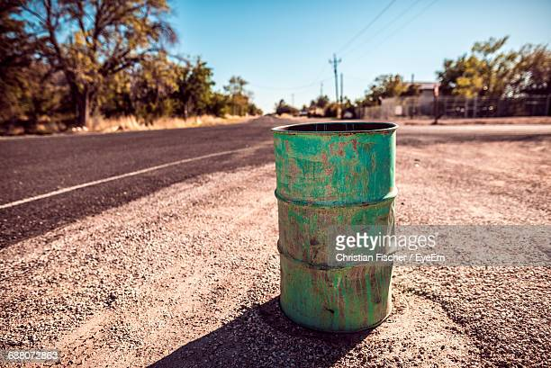 Abandoned Green Drum By Road On Sunny Day