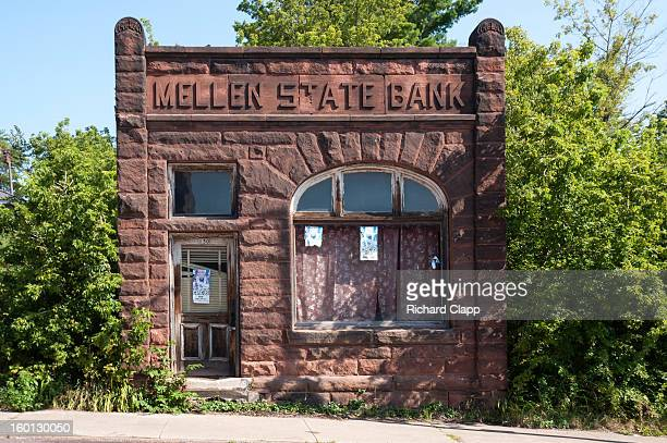 CONTENT] Abandoned historic brownstone building Mellen State Bank with encroaching vegetation on the main street of this small north western...