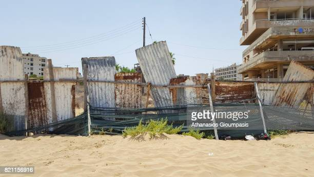 Abandoned hotel buildings stand beyond a makeshift barrier inside the 'Forbidden Zone' of Varosha district on July 11, 2017 in Famagusta, Cyprus....