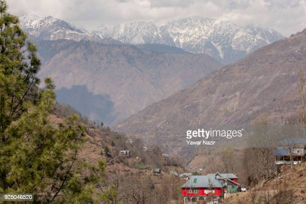 Abandoned houses stand in front the snow covered mountains during a fresh skirmish along the border on February 27 2018 in Silikote 120 Kms north...