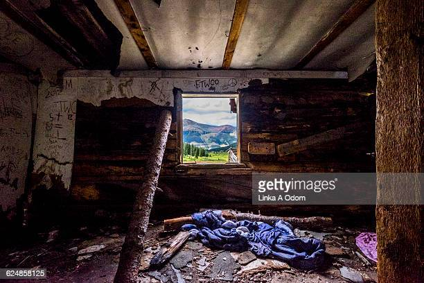 Abandoned log cabin with open window
