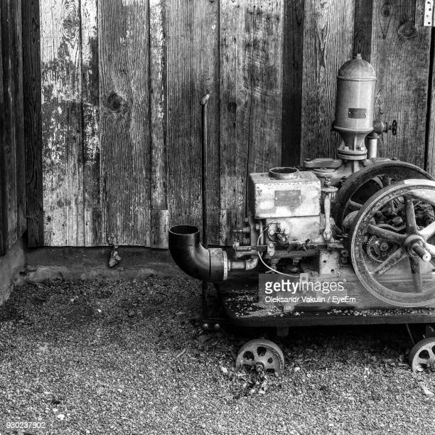 Abandoned Machinery Against Old House