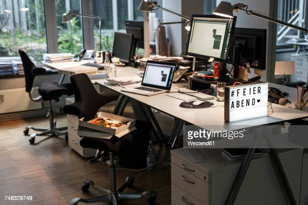 """Abandoned office with """"closing time"""" sign on desk"""