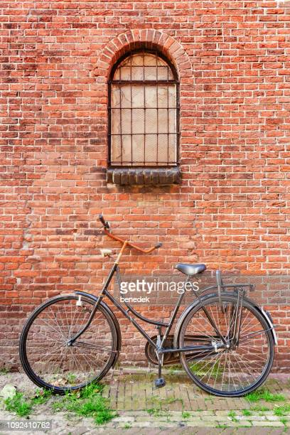 abandoned old bicycle in old town haarlem netherlands - haarlem stock photos and pictures