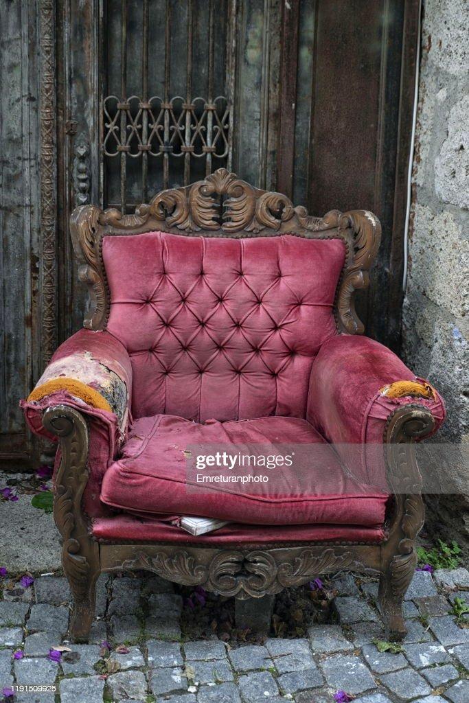 abandoned old purple velvet armchair in the street,Alacati. : Stock Photo