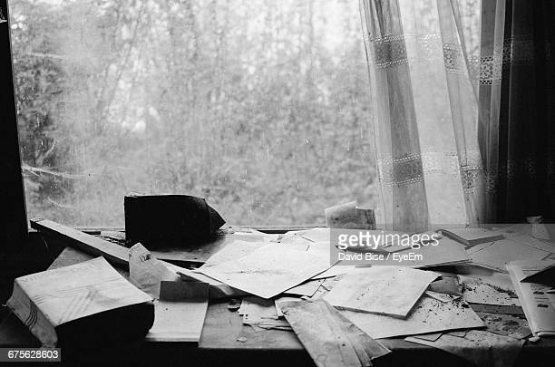 Abandoned Papers On Table Against Window