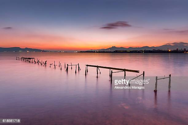Abandoned pier on calm sea at twilight