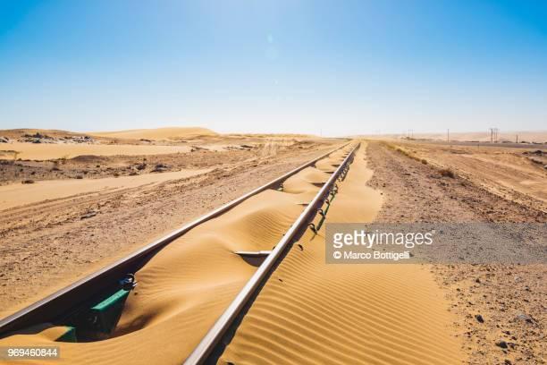 abandoned railway track going into the sand dunes, namibia - schienenverkehr stock-fotos und bilder