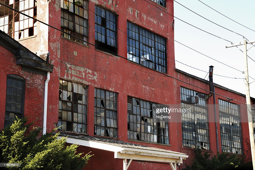 Abandoned red brick factory with broken windows : Stock Photo