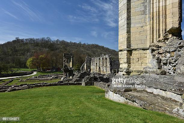 abandoned rievaulx abbey by grassy field on sunny day - rievaulx abbey stock pictures, royalty-free photos & images