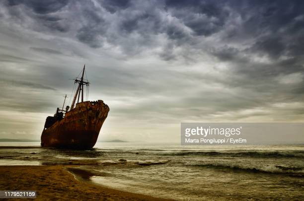 abandoned sailboat on sea shore against sky - shipwreck stock pictures, royalty-free photos & images