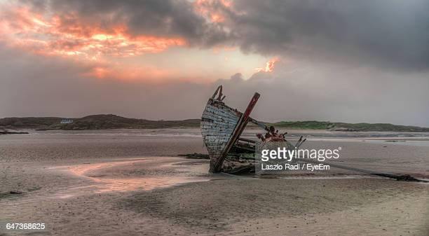 Abandoned Ship At Beach Against Cloudy Sky At Sunset