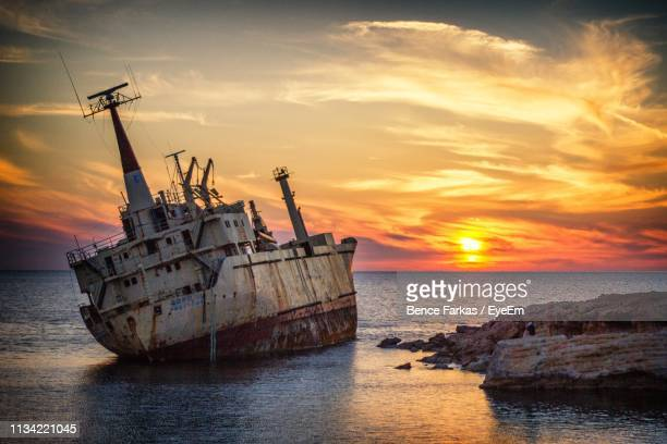 abandoned ship in sea against sky during sunset - cyprus stockfoto's en -beelden
