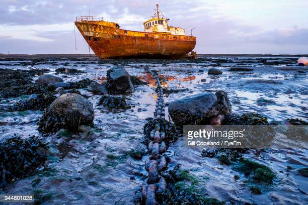 abandoned ship moored on sea against sky - barrow in furness stock photos and pictures