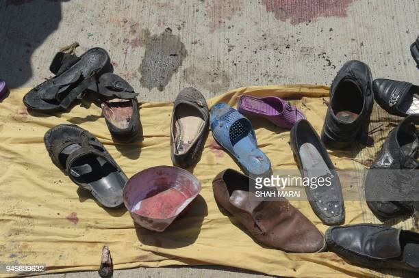 Abandoned shoes belonging to Afghan victims of a suicide bombing lie at the scene of the attack outside a voter registration centre in Kabul on April...