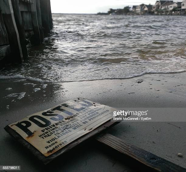 abandoned signboard lying on beach - mcconnell stock pictures, royalty-free photos & images