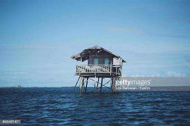 abandoned stilt house in sea against sky - run down stock pictures, royalty-free photos & images