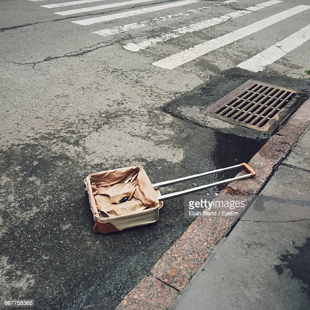 Abandoned Suitcase By Sewer On Street