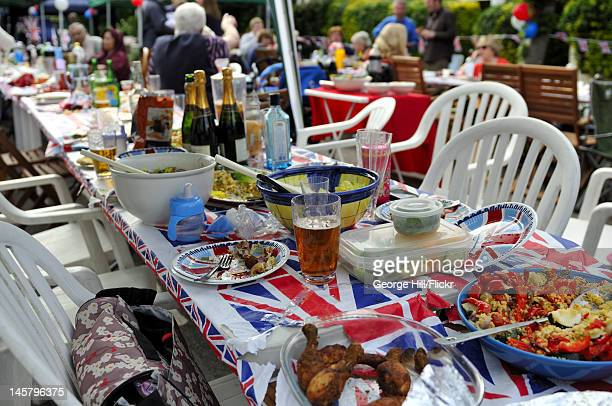 Abandoned table with leftover food and drink from a street party celebration in Melbourne Road, Wimbledon, South West London. The street party was...