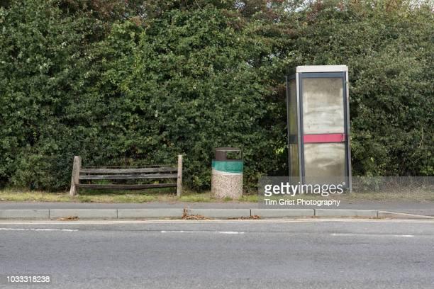 Abandoned Telephone Box, Broken Wooden Seat and Litter Bin on the Roadside