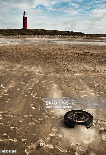 abandoned wheel at beach by lighthouse against sky - walter ciceri foto e immagini stock