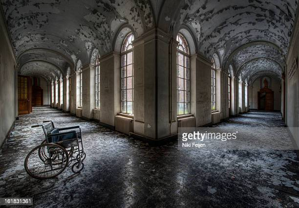 CONTENT] Abandoned wheelchair in the corridors of an derelict abandoned monastery with peeling paint