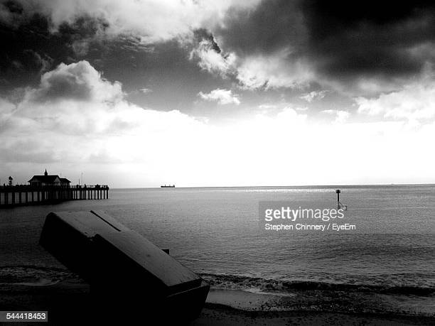Abandoned Wooden Cabinet On Beach Against Cloudy Sky