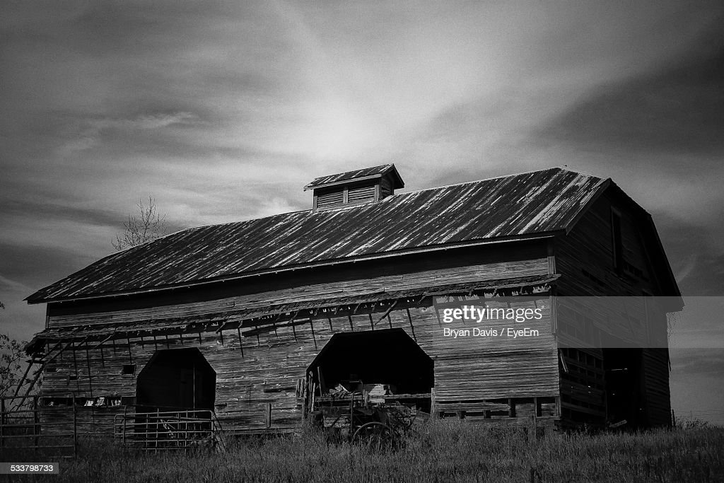 Abandoned Wooden House On Grassy Field Against Sky : Foto stock