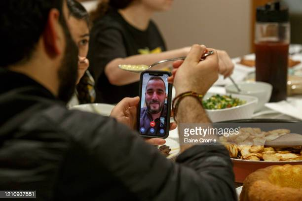 Abbas Al Haj Ahmed talks with his cousin Adam Bazzi over a video call while their family shares a meal and breaks fast on the first full day of...