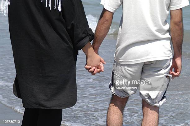 A couple hold hands while standing on the beach 2nd August 2003 Women are not allowed to swim in public places with swimming suits or bikini