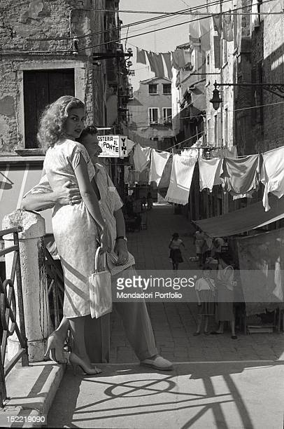 Abbe Lane and Xavier Cugat pose on a Venetian bridge the man hugs his wife and gazes into the distance while Abbe Lane looks to camera Venice 1956