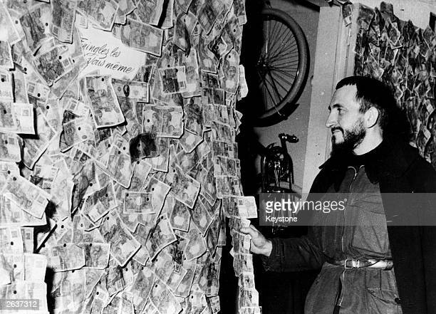 Abbe Pierre the priest and champion of the poor people of Paris admires the 'walls' of banknotes donated to a large Paris store which will go towards...