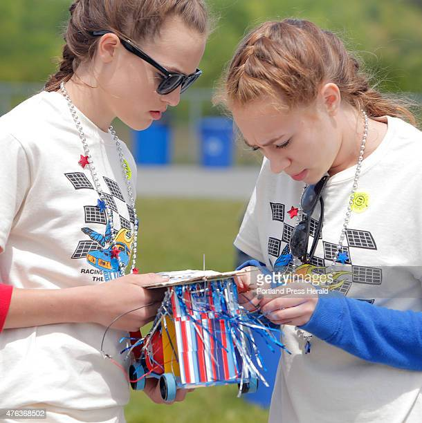 Abbie Baker, left, and Lauren Boubel, eighth graders at Bath Middle School, make adjustments to their solar race car before the start of a race heat...