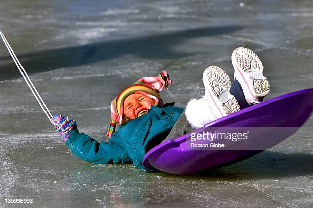 Abbie Boucher from West Bridgewater laughs as she tips off her coaster pulled across the ice by her dad Brian at the Francis D Howe at skating rink