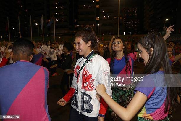 Abbie Brown of Great Britain dances with traditional Brazilian dancers during the teams official welcome and flag raising ceremony in the athletes...