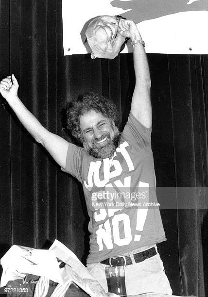 Abbie Hoffman holding a Ronald Reagan mask by the nose after his keynote speech at the CMJ Music Marathon Hoffman's shirt is in reference to Nancy...