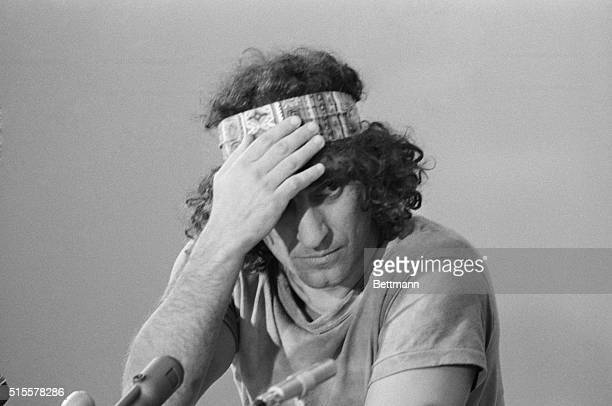 Abbie Hoffman, one of the eight men on trial for conspiracy to incite riots, appears to have a headache, as he adjusts Indian headband he wore during...