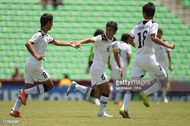 Abbosbek Makhstaliev of Uzbekistan celebrates with team-mate Kholmurod Kholmurodov after scoring the opening goal of the FIFA U-17 World Cup Round of...