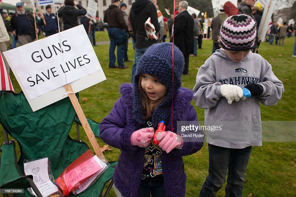 Abby and Emily, whose parents declined to provide a last name, play with the toy guns in their free gift bags provided by organizers during a pro-gun rally on January 19, 2013 in Olympia, Washington. The Guns Across America national campaign drew thousands of protesters to state capitols, including over 1,000 in Olympia.